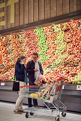 Man looking at woman talking on mobile phone while buying apples at supermarket - p426m1451832 by Maskot