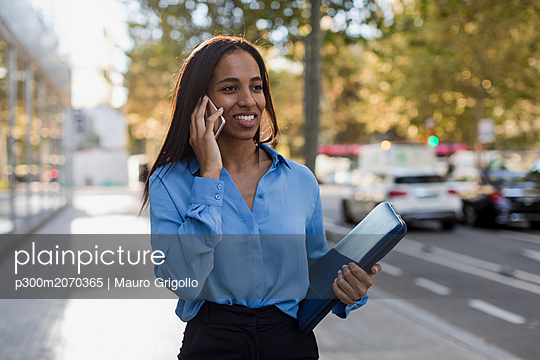 Businesswoman using smartphone, laptop bag - p300m2070365 by Mauro Grigollo
