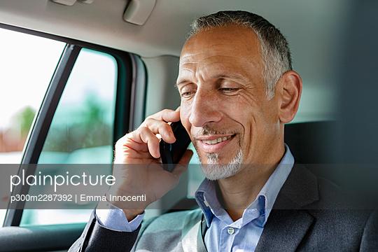 Businessman talking on smart phone in car - p300m2287392 by Emma Innocenti
