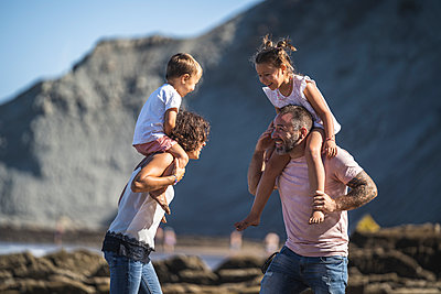 Cheerful parents carrying children on shoulder at beach - p300m2256621 by SERGIO NIEVAS
