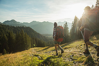 Austria, Tyrol, Tannheimer Tal, young couple hiking in sunlight on alpine meadow - p300m979049f by Uwe Umstätter
