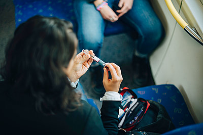 Woman checking injection pen while sitting in train - p426m1537164 by Maskot