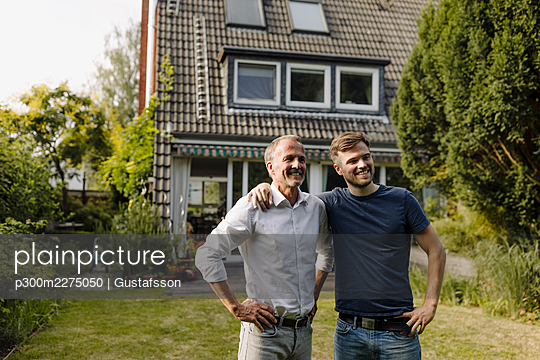 Smiling son and father with hand on hip standing in backyard during sunny day - p300m2275050 by Gustafsson