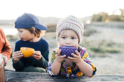 Adorable girl with brother drinking hot cocoa by woodden table at twilights - p1166m2095152 by Cavan Images