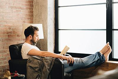 Mature man sitting barefoot in armchair, reading bok - p300m2202479 by Daniel González