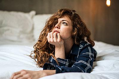 Junge Frau auf dem Bett denkt nach - p586m1144017 von Kniel Synnatzschke