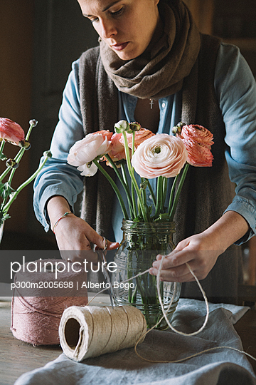 Woman arranging fresh flowers, cutting cord - p300m2005698 von Alberto Bogo