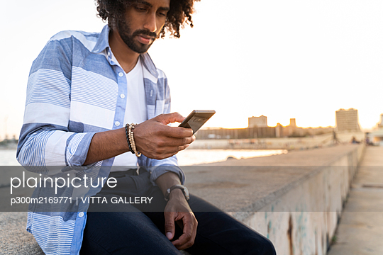 Young man sitting on quay wall at sunset using smartphone - p300m2169771 by VITTA GALLERY