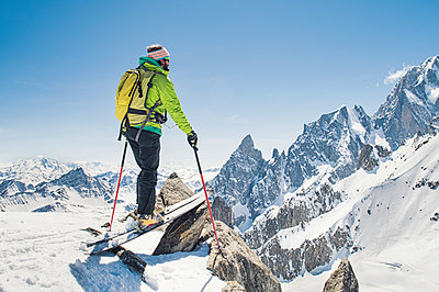Hiker with skis standing on snow covered mountain against clear blue sky during sunny day - p1166m1474119 by Cavan Images