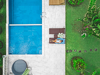 Aerial view of attractive woman near the pool at resort - p1166m2191861 by Cavan Images