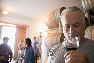 Senior male vintner smelling and tasting red wine in winery barrel room - p1192m1183813 by Hero Images