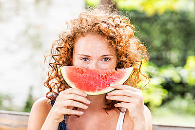 Portrait of redheaded young woman with watermelon - p300m2029051 by Jo Kirchherr