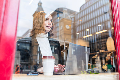 Businesswoman using laptop at a cafe in the city - p300m2181210 by William Perugini