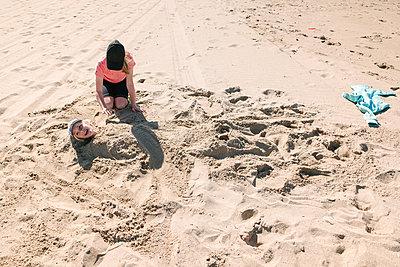 Girl burying brother in sand on beach - p924m2271143 by Viara Mileva