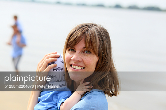 Mother carries baby in her arms - p1258m2204678 by Peter Hamel