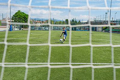 Boy kicking soccer ball against sky seen through net - p1166m2011281 by Cavan Images