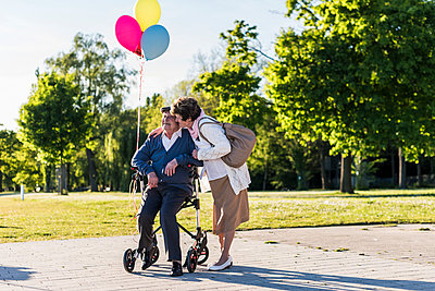Happy senior couple with balloons - p300m1460095 by Uwe Umstätter