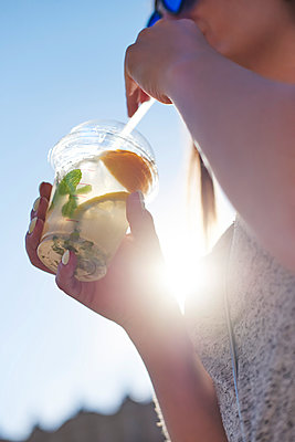 Woman drinking lemonade from plastic cup, close-up - p300m2012196 by gpointstudio