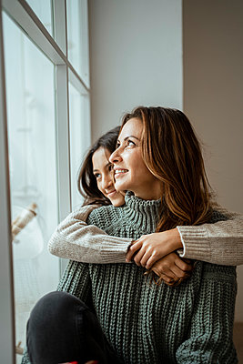Happy mother and daughter looking through window while day dreaming together at home - p300m2256509 by Rafa Cortés