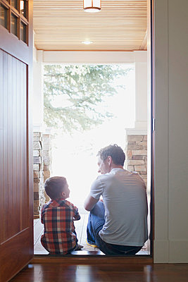 Father and son sitting in doorway. - p328m717947f by Hero Images