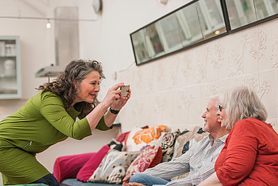 Happy seniors taking photograph on couch - p429m1206863 by Colin Hawkins