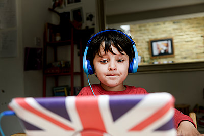 A five year old boy in blue headphones having an interactive learning session, home schooling.  - p429m2191099 by Bonfanti Diego