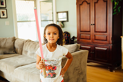 Mixed race girl holding light-saber in living room - p555m1306253 by Inti St Clair