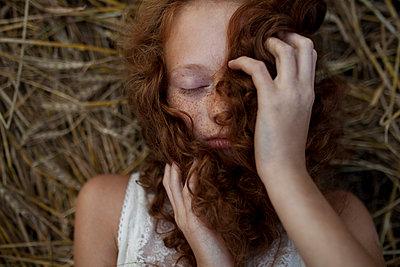 Caucasian girl laying in wheat holding hair - p555m1521599 by Vyacheslav Chistyakov