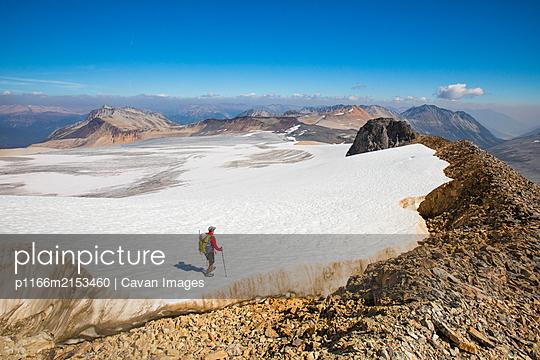 high angle of backpacker hiking across tip of huge glacier. - p1166m2153460 by Cavan Images