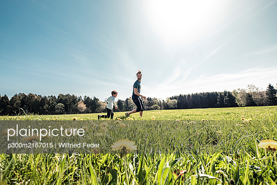 Father and little son having fun together on a meadow in spring - p300m2167015 by Wilfried Feder