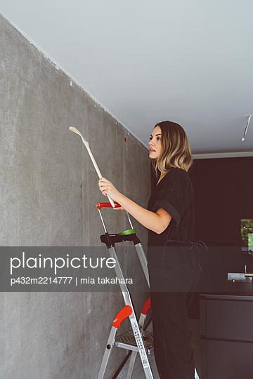 Junge Frau steht mit Pinsel auf Leiter - p432m2214777 von mia takahara