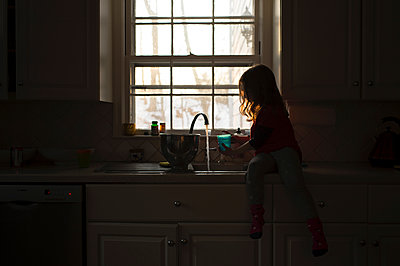 Girl playing with water at kitchen sink - p1166m1423387 by Cavan Images