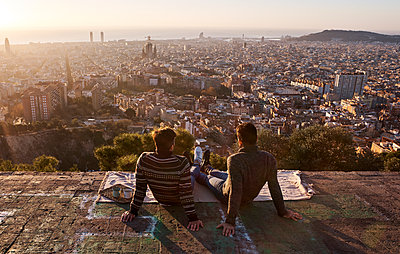 Gay boyfriends looking at crowded cityscape while sitting on viewpoint, Bunkers del Carmel, Barcelona, Spain - p300m2256687 by Veam