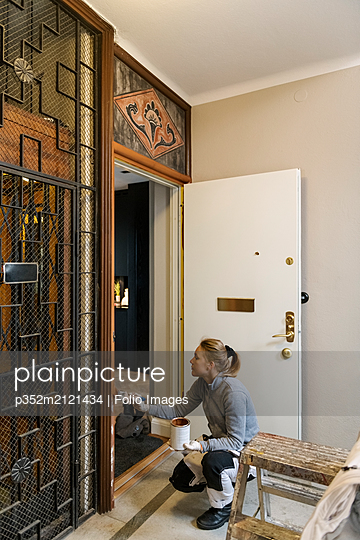 Painter painting door frame in apartment building - p352m2121434 by Folio Images