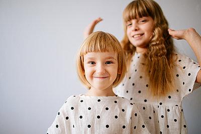 Zwei Mädchen in gepunkteten Kleidern - p1414m2044851 von Dasha Pears