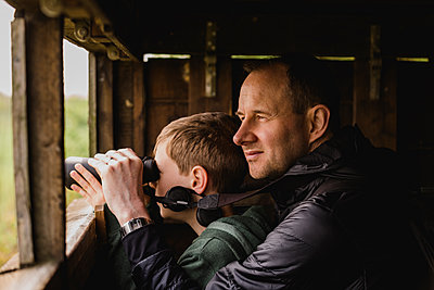 Boy and father birdwatching with binoculars - p300m1449681 by Nicole Matthews