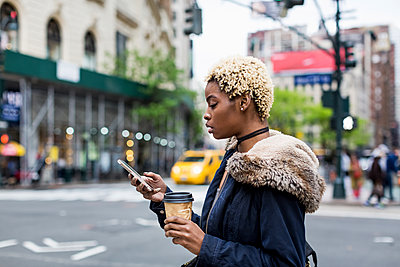 USA, New York City, fashionable young woman with coffee to go looking at cell phone on the street - p300m1537262 by Mauro Grigollo