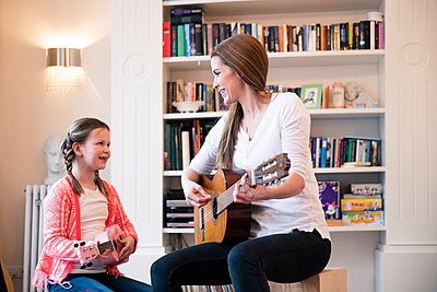 Mother and daughter playing guitar together at home - p300m1588083 von Robijn Page