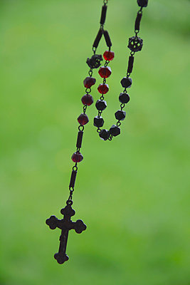 Rosary in front of blurred green background - p300m980263 by Axel Ganguin