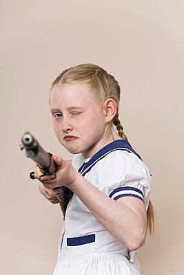 A tough girl wearing a sailor dress aiming a rifle at the camera - p301m844167f by Paul Hudson