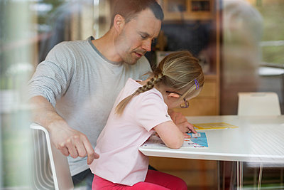 Father assisting handicapped girl in studies at table - p426m927825f by Maskot