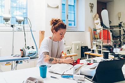 Fashion designer working in her studio - p429m2058380 by Eugenio Marongiu