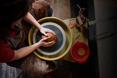 Caucasian woman shaping pottery clay on wheel - p555m1481943 by JGI/Jamie Grill