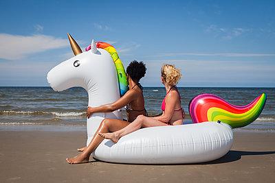 Zwei Freundinnen sitzen auf Einhorn am Meer - p045m1590311 von Jasmin Sander