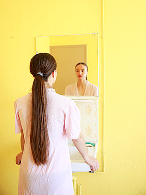 Woman in nightgown in front of mirror - p1105m2082545 by Virginie Plauchut