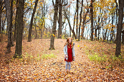 Young Red Hair Girl Playing Outside in Fall Leaves - p1166m2147055 by Cavan Images