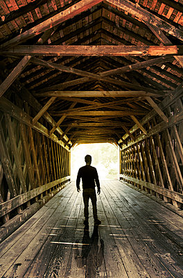 Man stands on roofed bridge  - p1248m1491862 by miguel sobreira