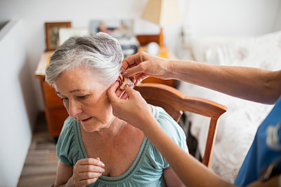 Nurse putting hearing aid to a senior woman in a retirement home - p1315m1186283 by Wavebreak