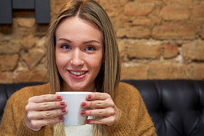 Beautiful woman having coffee at cafeteria - p300m2256724 by Veam