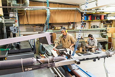 Mature carpenter working with machinery while colleague using laptop in workshop - p300m2293670 by Eugenio Marongiu